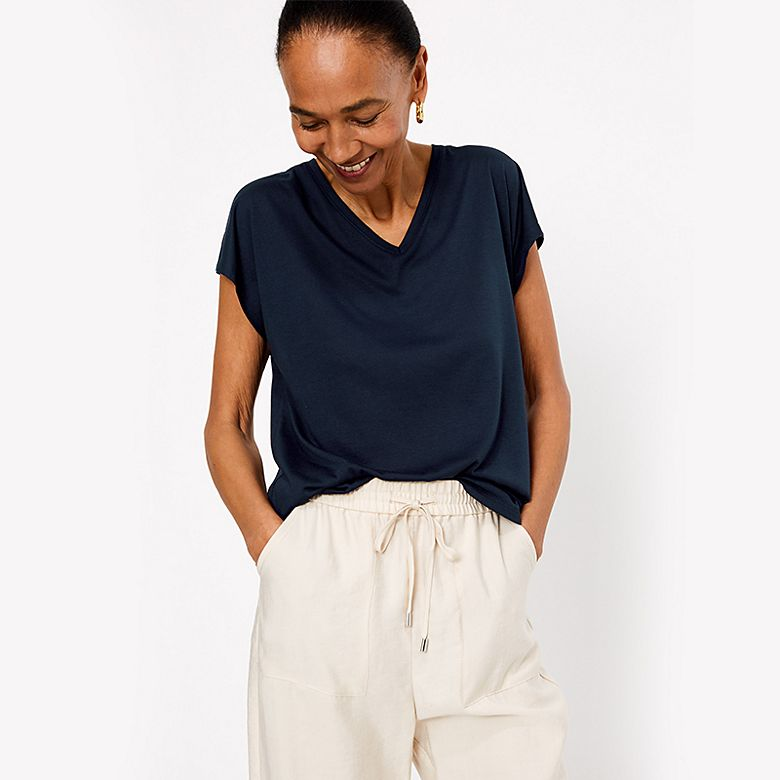 Woman wearing navy V-neck T-shirt and cream joggers