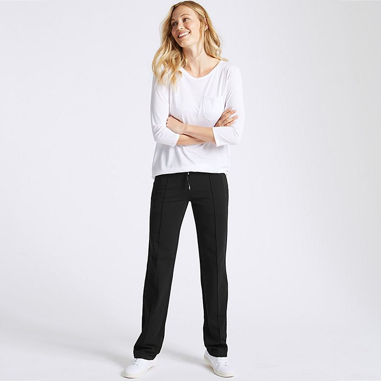Woman wearing white long-sleeved T-shirt and black joggers