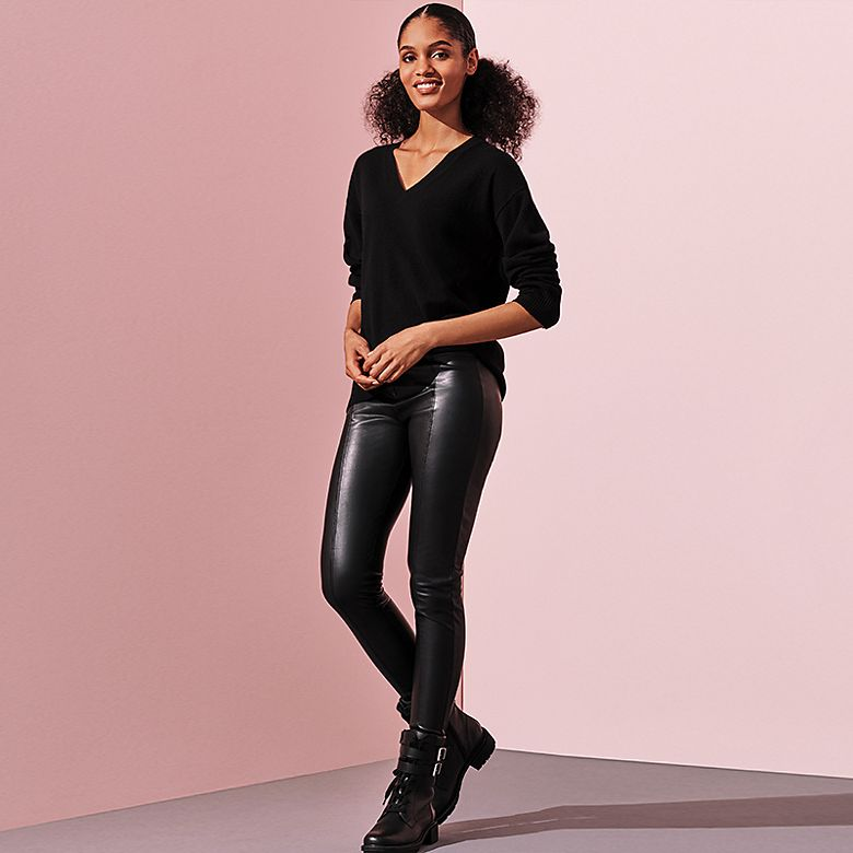 Woman wearing black V-neck sweater and black PU leggings