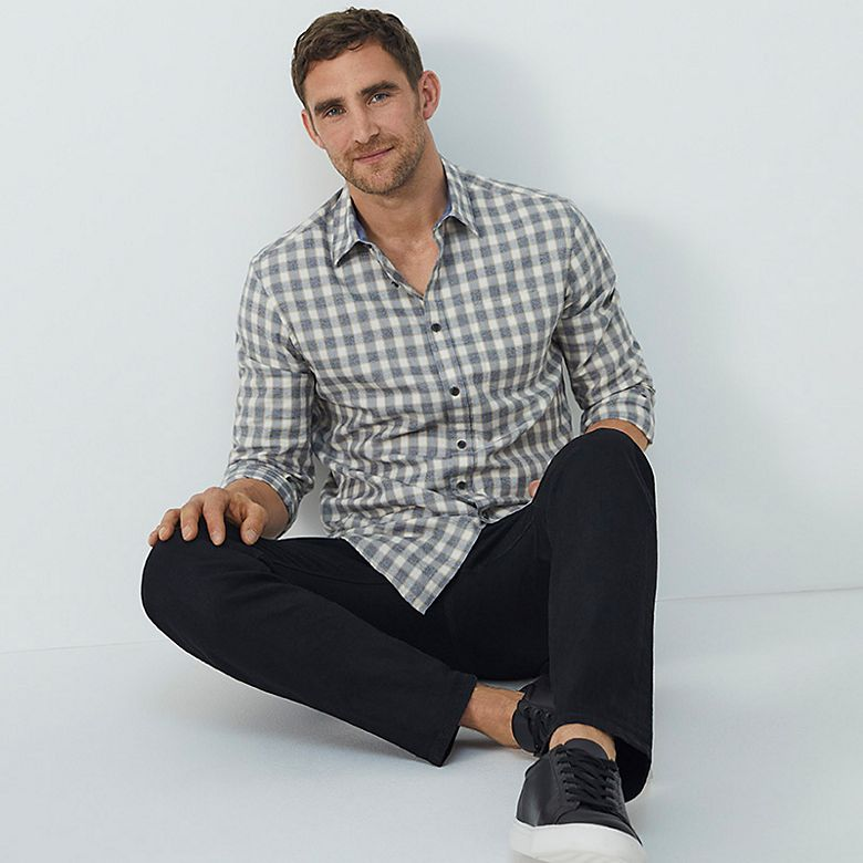 Man wearing checked shirt and black jeans