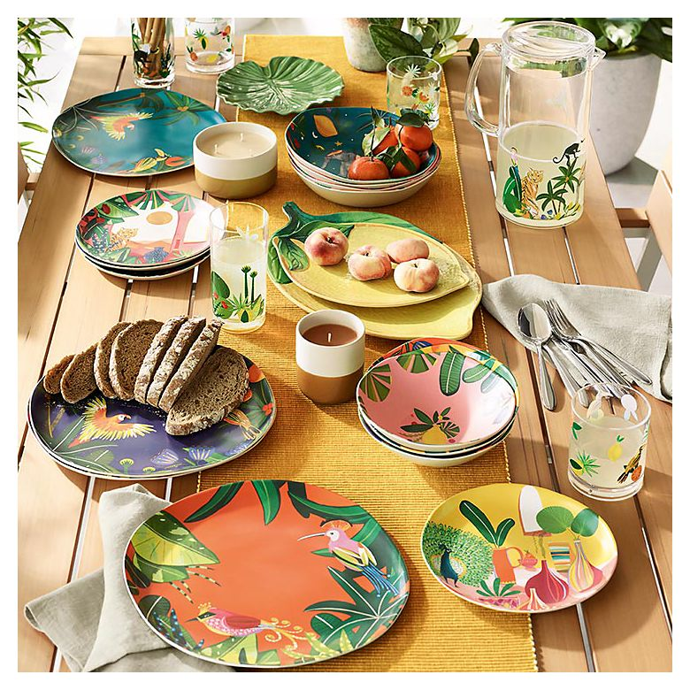 Wooden table set with jungle-themed picnicware, lemon-shaped picnic platters and picnic glasses