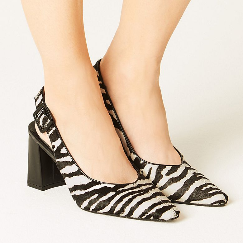Woman wearing black and white zebra-print sling-back shoes
