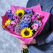 A man holds a bunch of bright summer flowers