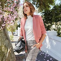 Woman wearing a pink blazer, white roll neck and grey checked trousers