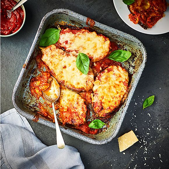 A tray of aubergine parmigiana with fresh basil and parmesan