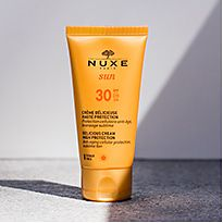 Bottle of Nuxe sunscreen against a grey background
