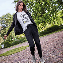 Woman walking in a park wearing a printed T-shirt, jacket, joggers and trainers