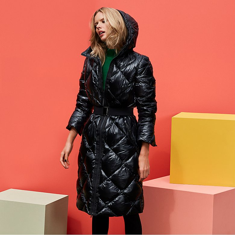 Model wears black padded knee-length coat