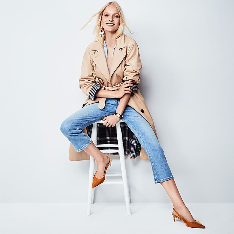 Model Myrthe De Poel wears beige trench coat, cropped flare jeans and pointed velvet heels