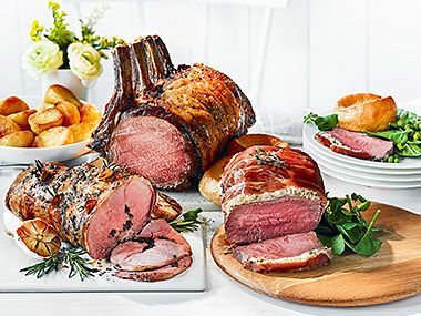 A selection of roasted joints with roast potatoes, Yorkshire puddings and greens