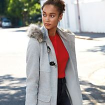 Woman wears a grey duffle coat with faux-fur trim