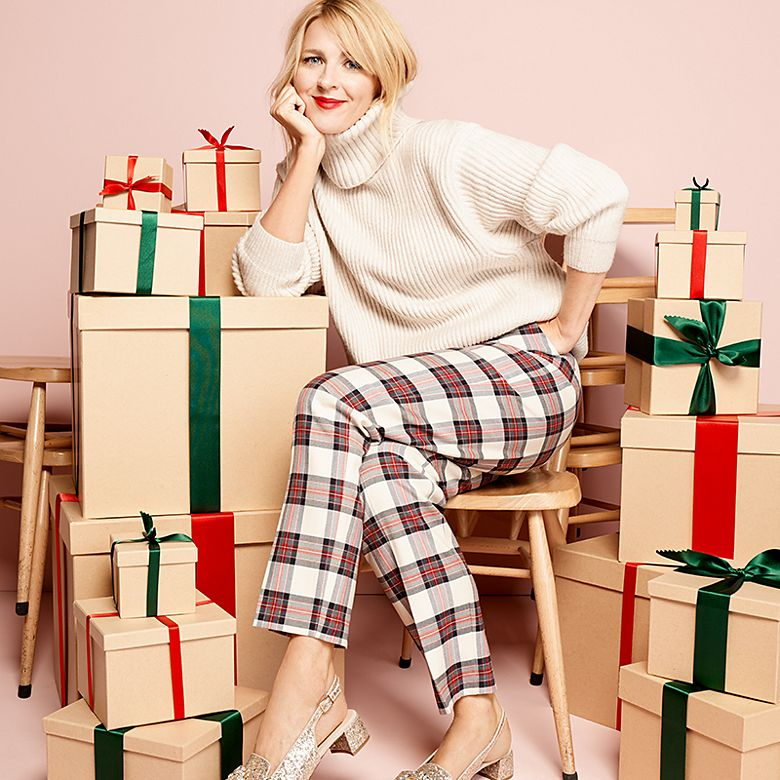 Sarah wears cream roll-neck jumper and tartan trousers