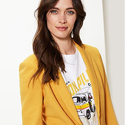 Woman wearing yellow blazer and printed T-shirt