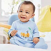 Baby boy wearing a blue caterpillar-print sleepsuit