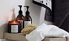Calm scented candle, hand wash and hand lotion in bathroom