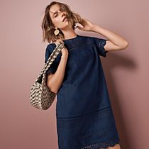 Woman wearing a navy embroidered shift dress and a woven bag