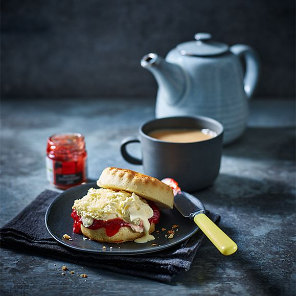 A scone with clotted cream and jam served alongside a pot and cup of tea