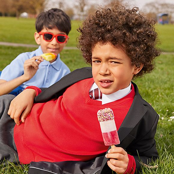 Two children wearing M&S school uniform eating ice lollies
