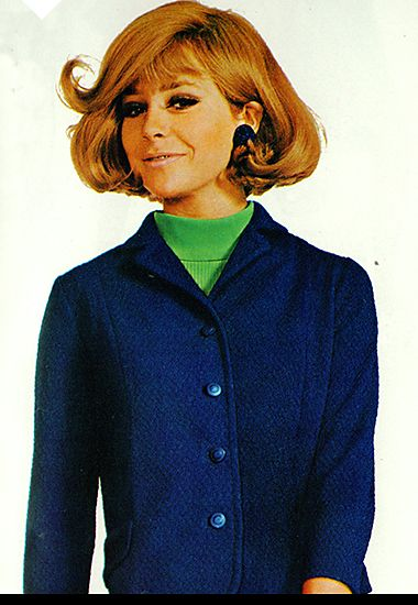 Woman wearing a blue wool skirt suit with a green top, 1967