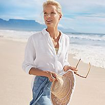 Woman wearing a white linen shirt and blue linen shorts