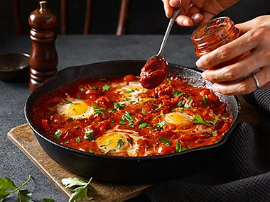 A tray of shakshuka with a person spooning in M&S smoked tomato paste