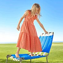 Girl stood on a sun chair wearing an orange summer dress
