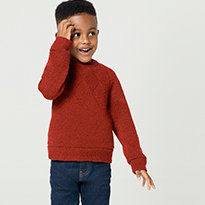 Boy wears a red jumper and jeans