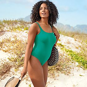 Woman on a beach wearing a bright green swimsuit
