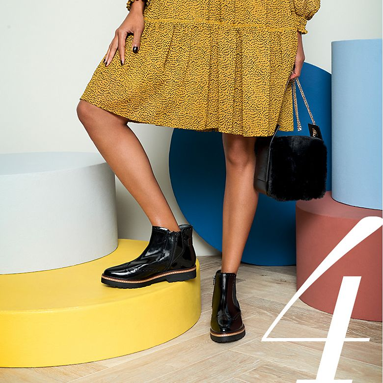 Model wears black Chelsea boots with a mustard-yellow dress