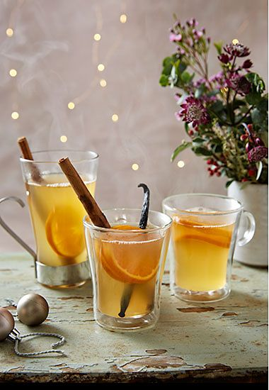 Mulled cider with cinnamon stick, vanilla and orange slices