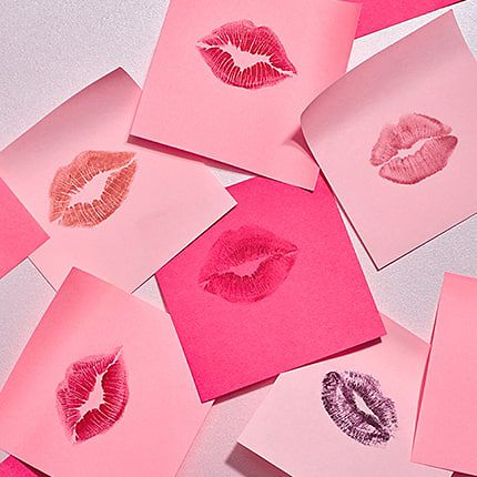 Multiple lipstick prints on pink pieces of paper