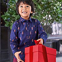 Boy wearing a blue printed shirt holds a Christmas gift