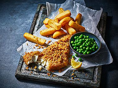 Beer-battered cod, scraps, peas and a lemon wedge