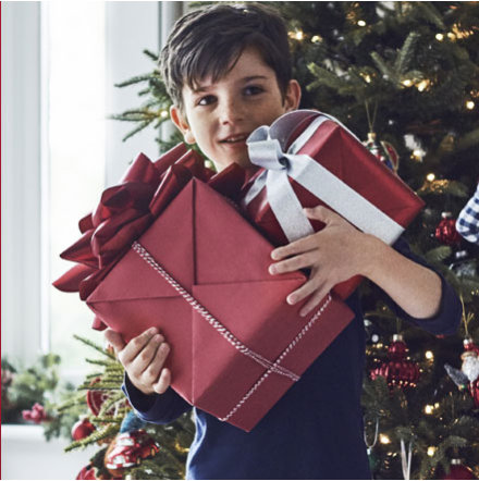A boy holding Christmas presents