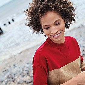 Woman on a beach wearing a red and beige colour-block jumper