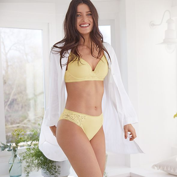 Woman wearing an open white shirt, yellow bra and matching knickers
