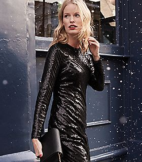Woman in the snow wears a black sequin dress