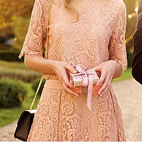 Woman in coral lace dress holding a gift