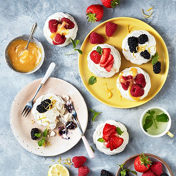 A selection of meringue nests topped with summer berries, cream and lemon curd