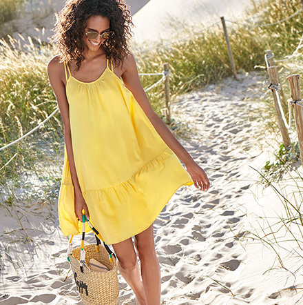 Woman wearing a yellow dress on the beach