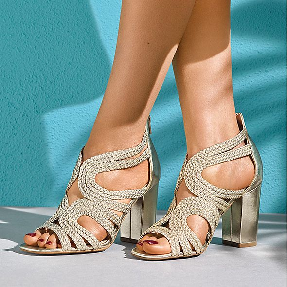 Model wearing a pair of gold block-heel braided sandals