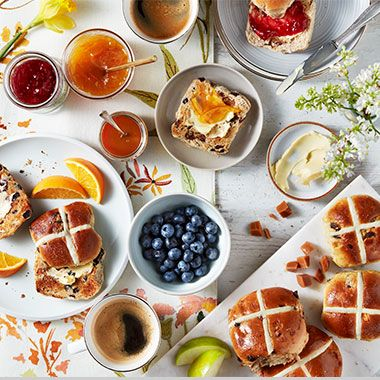 Selection of hot cross buns with fresh fruit and jams