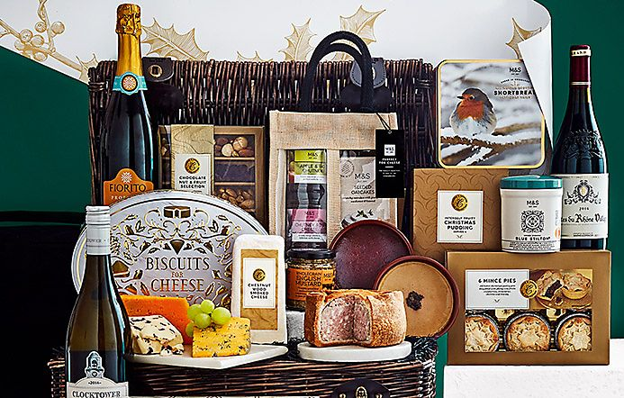 Wicker hamper surrounded by treats and wine