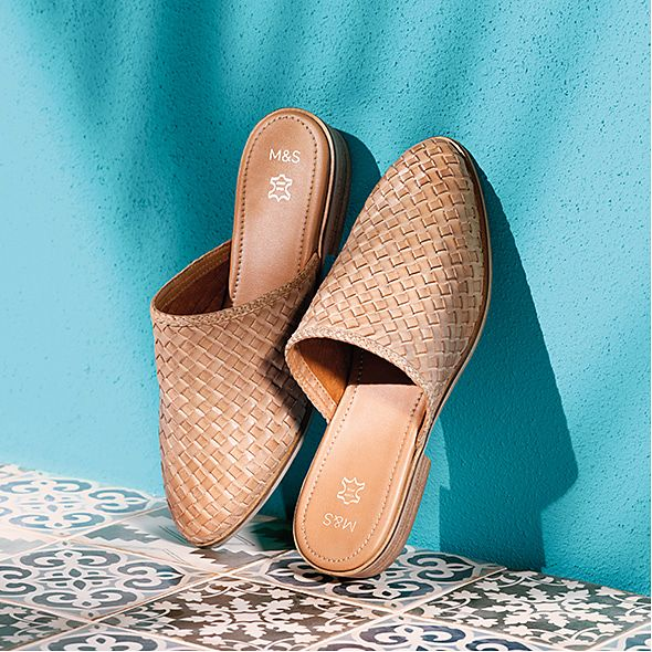 Tan leather woven mules leaning against a blue wall