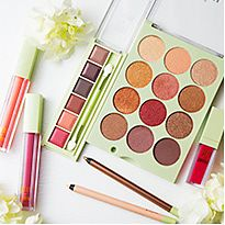 A selection of Pixi make-up next to fresh flowers
