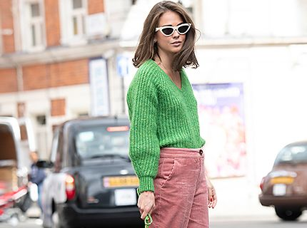 Woman wears pink wide-leg trousers and a green sweater.