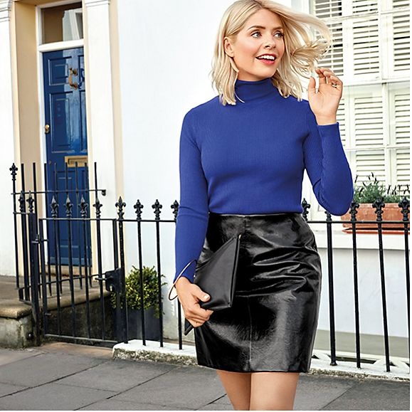 Holly Willoughby wearing a blue roll-neck jumper, black patent mini skirt and a black ring-detail clutch bag