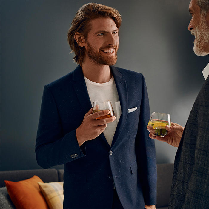Man wearing navy blue suit drinking a cocktail