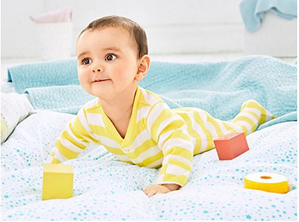 Baby lying on a blanket wearing a yellow and white striped sleepsuit