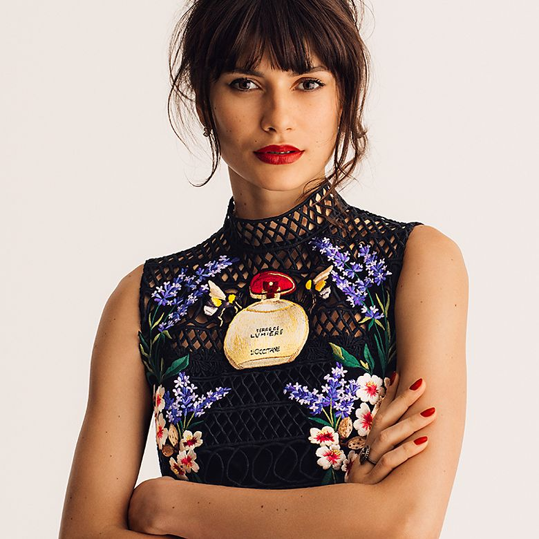 Woman wearing a black evening dress with floral, bees and a bottle of L'Occitane perfume embroidery